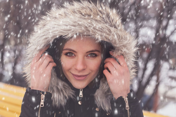 Woman and snow in winter Portrait Winter Headshot Looking At Camera Cold Temperature Fur Warm Clothing Smiling One Person Front View Hat Happiness Clothing Fur Hat Young Adult Lifestyles Real People Snow Fur Coat Hood - Clothing Snowing Beautiful Woman
