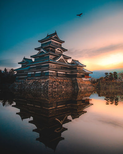 A beautifully calm and cold winter morning at Matsumoto Castle. As the birds flew over head and the swans swam past it only added to the serenity. Castle Japan Japan Photography Serenity The Traveler - 2018 EyeEm Awards Animal Architecture Belief Bird Building Building Exterior Built Structure Cloud - Sky Lake Nature No People Outdoors Place Of Worship Reflection Religion Sky Spirituality Sunset Water Waterfront