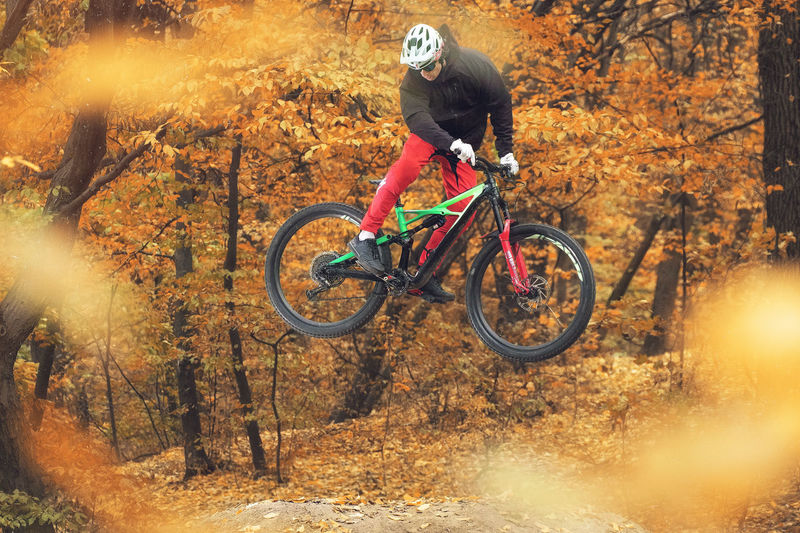 Man riding bicycle in forest during autumn