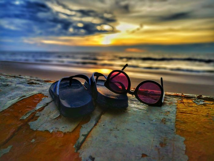 Close-up of sunglasses on sand at beach against sky during sunset