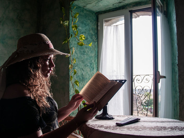 Woman Reading Book While Sitting At Home