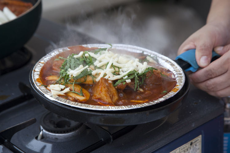 Cropped image of woman preparing food in foil container on stove at street