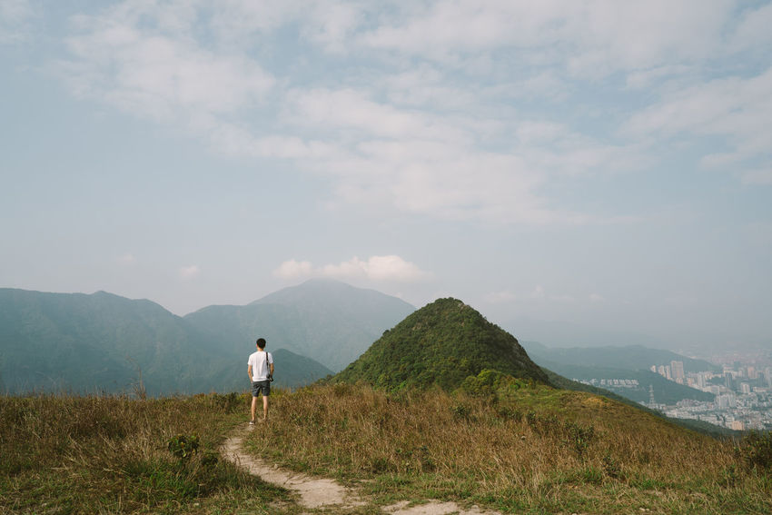 Mountain and Man Adventure Beauty In Nature Day Full Length Grass Landscape Lifestyles Men Mountain Nature One Person Outdoors People Real People Rear View Sky Standing Walking