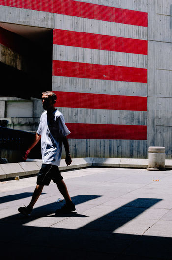 STRIPES Full Length One Person Shadow Built Structure Real People Sunlight Day Casual Clothing Lifestyles Architecture Building Exterior City Road Walking Street Side View Nature Outdoors Footpath Shorts Streetphotography Street Photography EyeEm Best Shots EyeEm Selects The Street Photographer - 2019 EyeEm Awards
