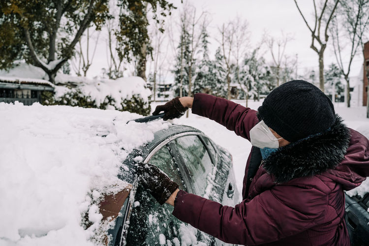 Rear view of person holding umbrella during winter