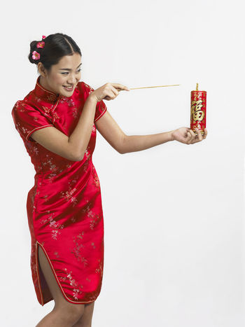 young chinese woman playing decoration firecracker for fun Fun Gong Xi Fa Cai Happiness Mischief Prosperity Traditional Clothing Cheongsam Chinese Ethnicity Chinese New Year Decoration Fire Firecracker Greetings Joss Stick Playing Qipao Smile Smiling Traditonal Festival Young Adult Young Woman