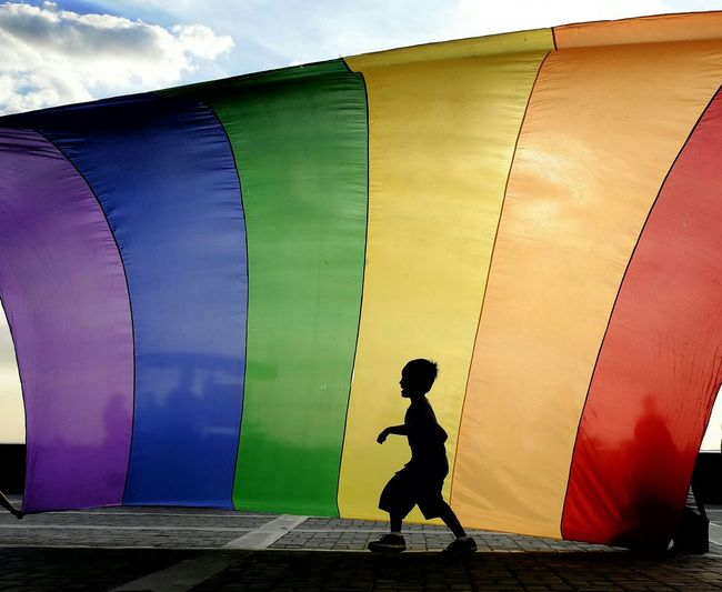 Side View Of Silhouette Boy Walking Against Colorful Textile On Footpath