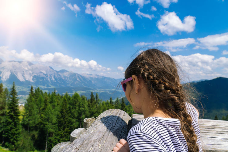 Girl hiking on beautiful summer day in alps mountains austria,  admire amazing view to mountain peak