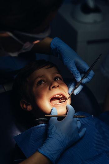 Dentist operating boy in medical clinic