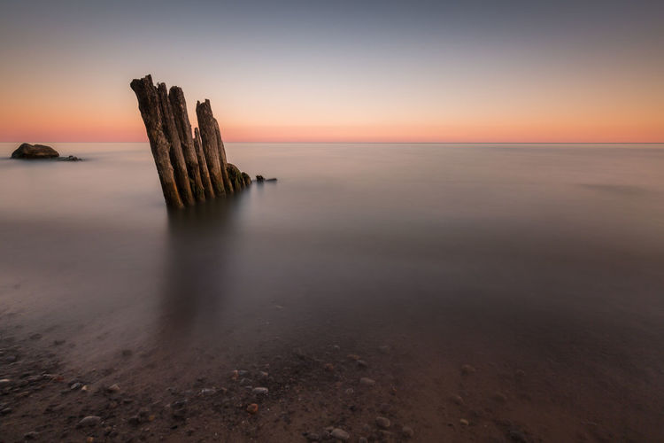 Damaged Wooden Post At Beach Against Clear Sky During Sunset