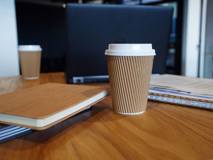 Close-Up Of Disposable Coffee Cup Against Laptop On Table