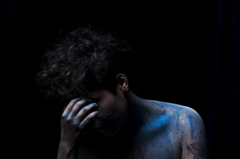 Close-up of man covered with powder paint against black background