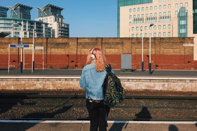 Rear view of woman with backpack standing at railroad station platform in city