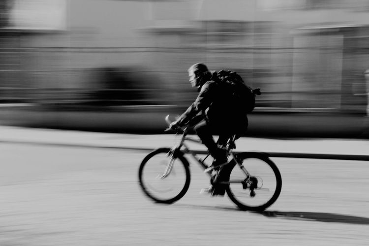 Close-up of silhouette man on bicycle on street