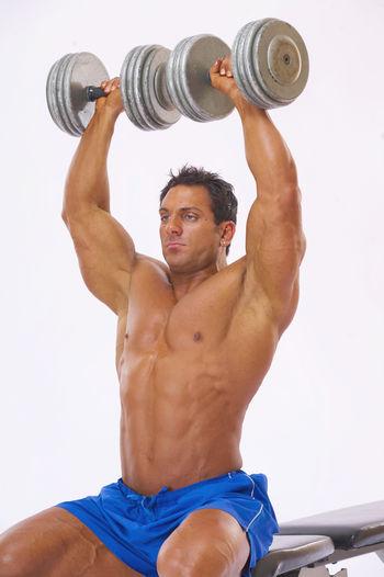 Shirtless man lifting dumbbells while sitting against white background