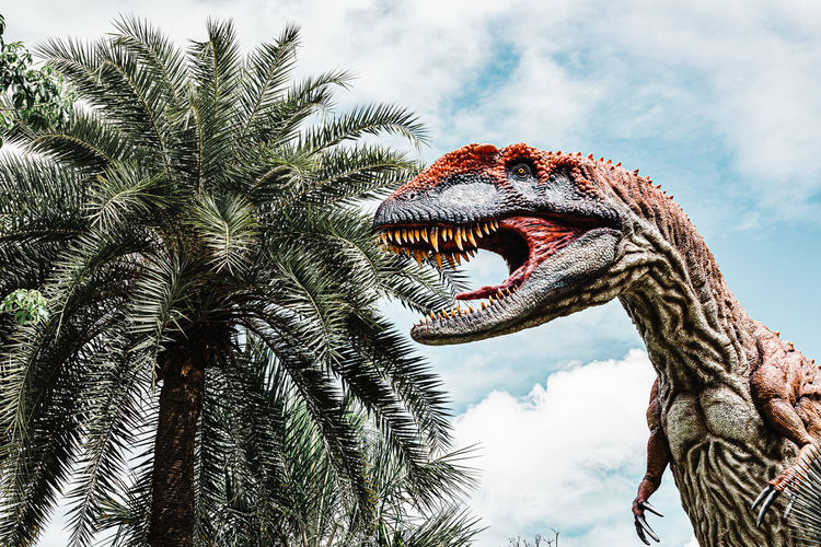 Low angle view of dinosaur statue against sky