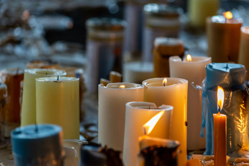 Close-up of lit tea candles in temple