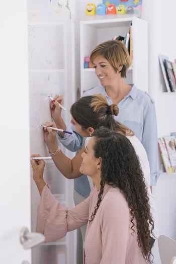 Female psychotherapists writing on whiteboard