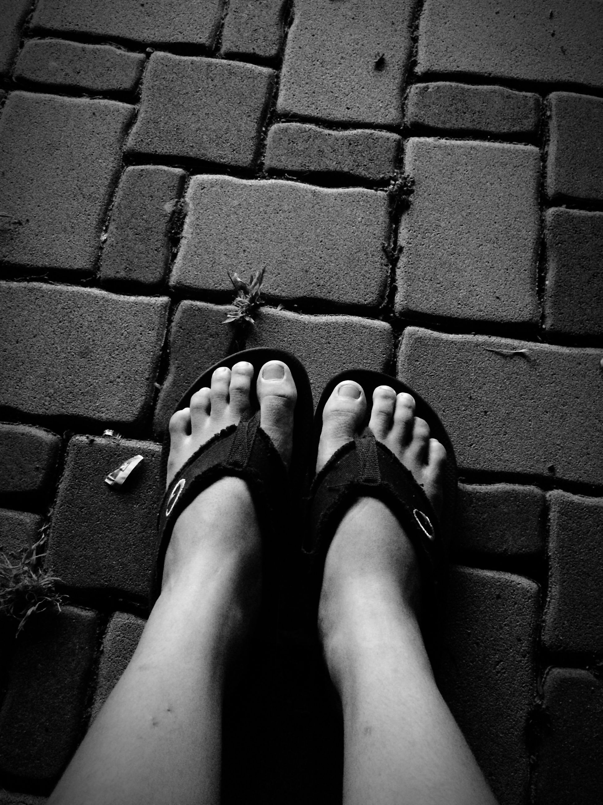 low section, person, shoe, personal perspective, human foot, high angle view, footwear, standing, lifestyles, directly above, street, tiled floor, leisure activity, cobblestone, human limb, part of