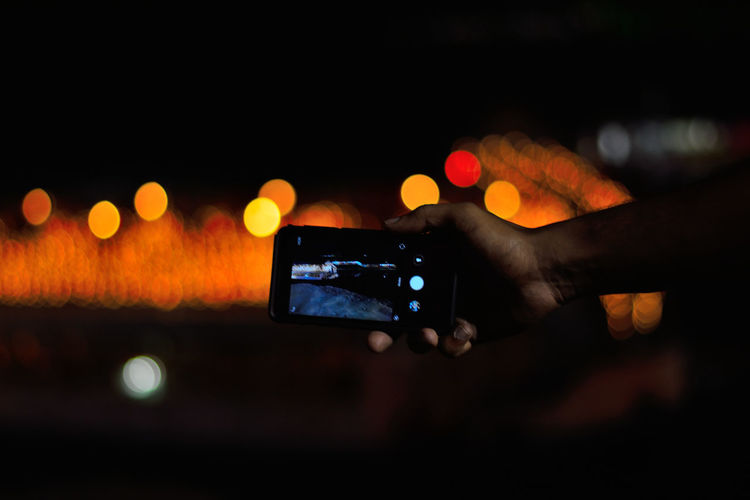 Close-up of hand using smart phone at night