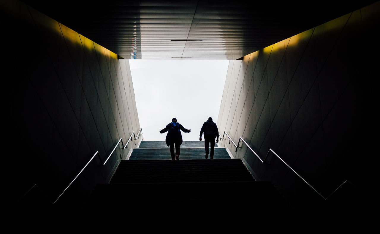 Low angle view of men walking on steps