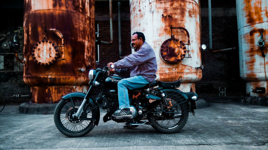 Side view of man riding motorcycle on street