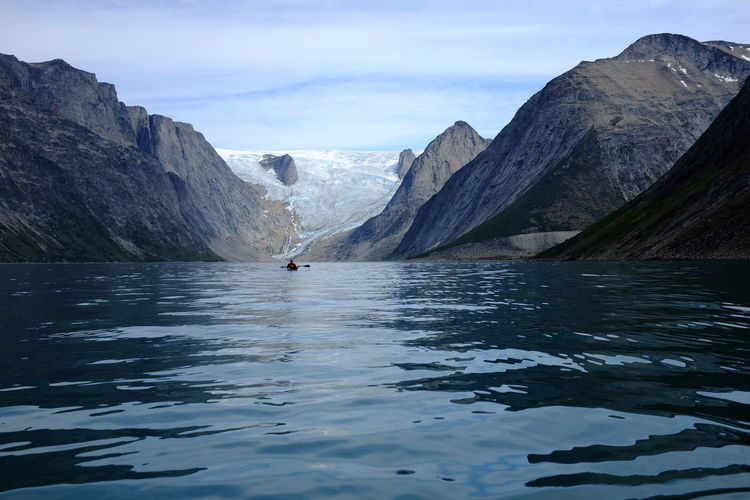 Distant Person Kayaking On Sea Against Mountains