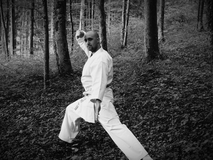 Portrait of young man practicing karate in forest