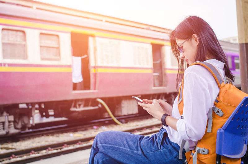 Side View Of Woman Using Mobile Phone At Railroad Station