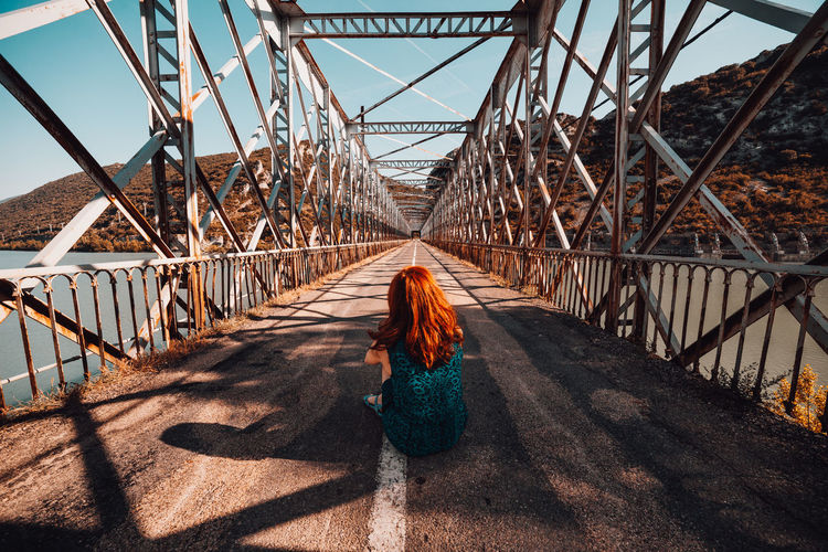 Rear view of woman sitting on footbridge against sky