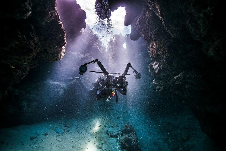 Scuba diver swimming amidst coral in sea