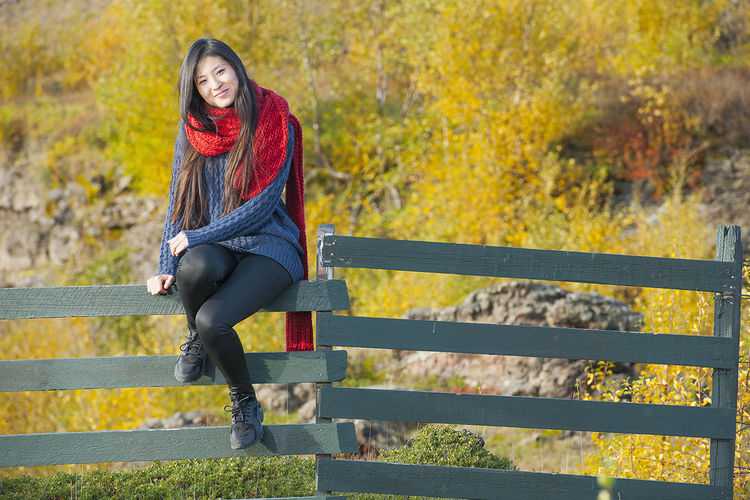 Full length of a woman sitting on autumn leaves