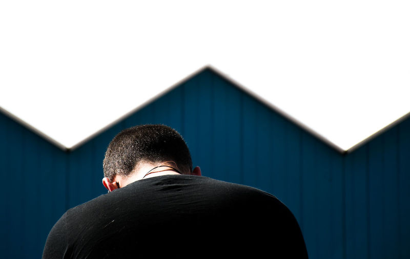Rear view of man standing by house against building