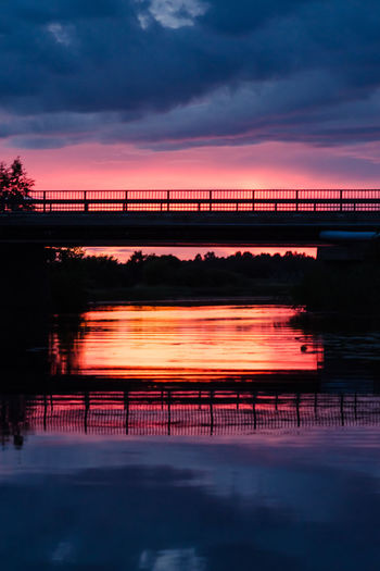 Bridge over river against sky at sunset