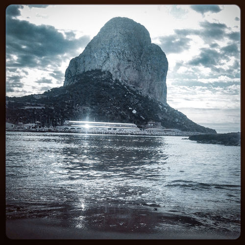 Calp rock revisited Calpe Alicante España Mediterranean  Monochrome Glittering Glinting Sunlight Mediterranean Sea Landmark Mountain Headland Water Sea Beach Sand Sky Cloud - Sky Rock Formation Wave Rocky Mountains Rock Rugged Coast Geology Rocky Coastline Eroded