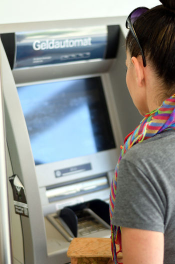 Side View Of Mature Woman Using Atm