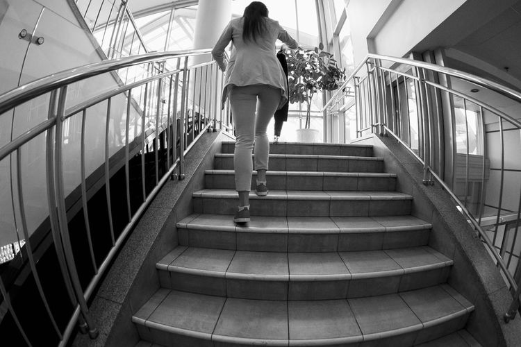 Rear View Of Woman Moving Up On Staircase