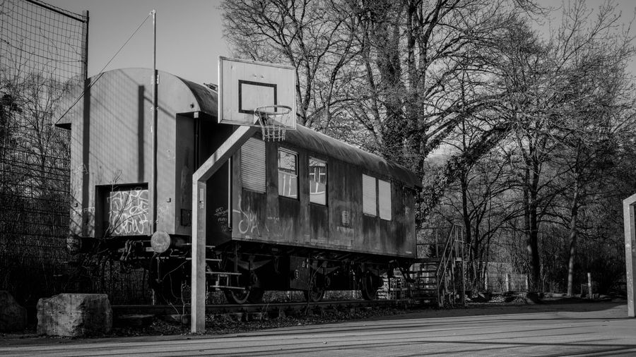 Retired Basketball Court Basketball Schulhof Schule Tübingen Schwarzweiß Blackandwhite SEL35F18 SonyAlpha6000 Wagon  Train Bare Tree Built Structure Abandoned Outdoors Architecture Transportation Mobility In Mega Cities Day No People Building Exterior Tree Sky Colour Your Horizn Visual Creativity