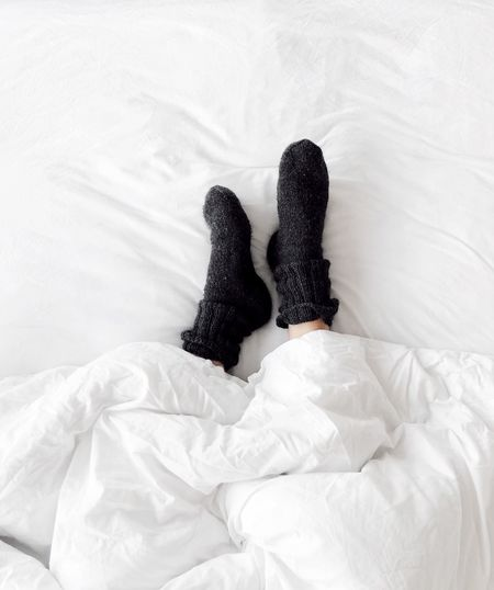 Low Section Of Person Wearing Socks While Lying Down On Bed