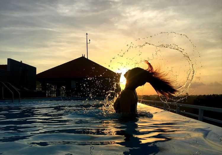 Woman in swimming pool against sky during sunset