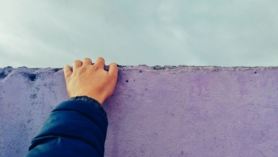 Cropped Image Of Man On Purple Retaining Wall Against Sky