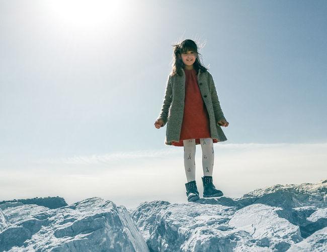 Full length of girl standing on rocks against sky during winter