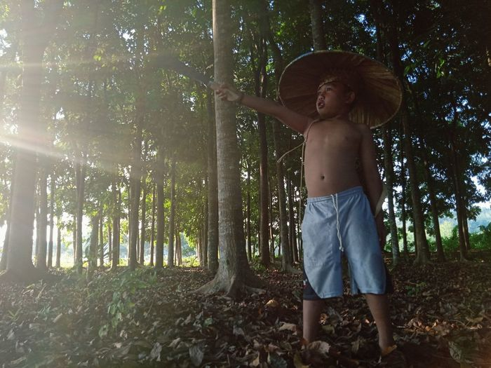 Full length of shirtless boy holding weapon standing in forest
