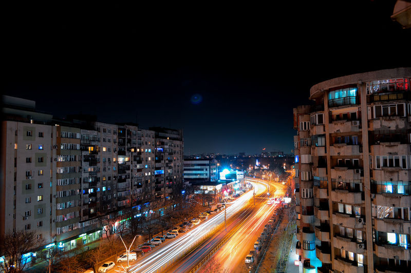 Light trails on road amidst buildings in city at night