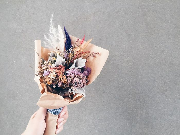 Cropped hand holding bouquet against wall