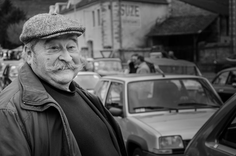 Mature man standing by cars on city street