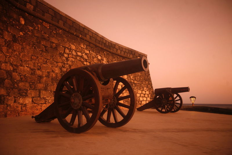 Cannons by stone wall against sky at sunset