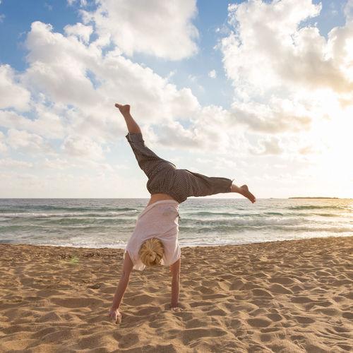 Full length of man skateboarding on beach against sky