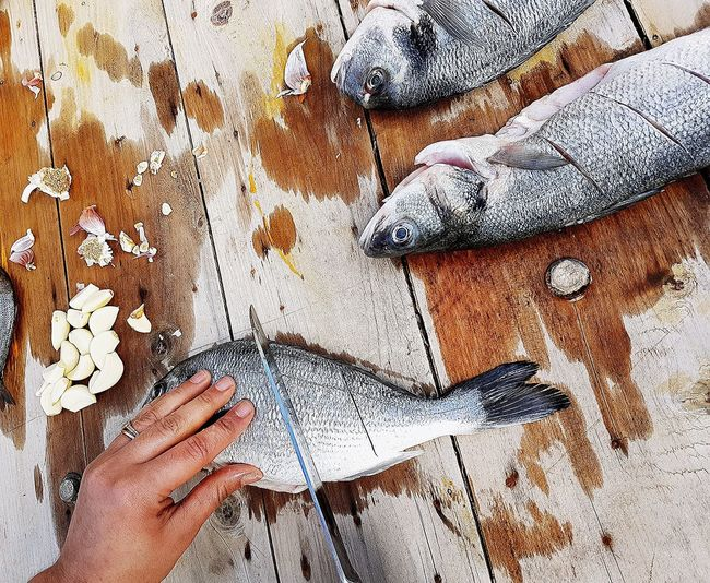 Cropped hand of woman chopping fish on wooden table