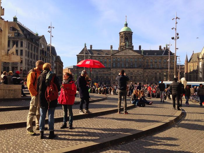 Crowd at dam square with royal palace of amsterdam against sky